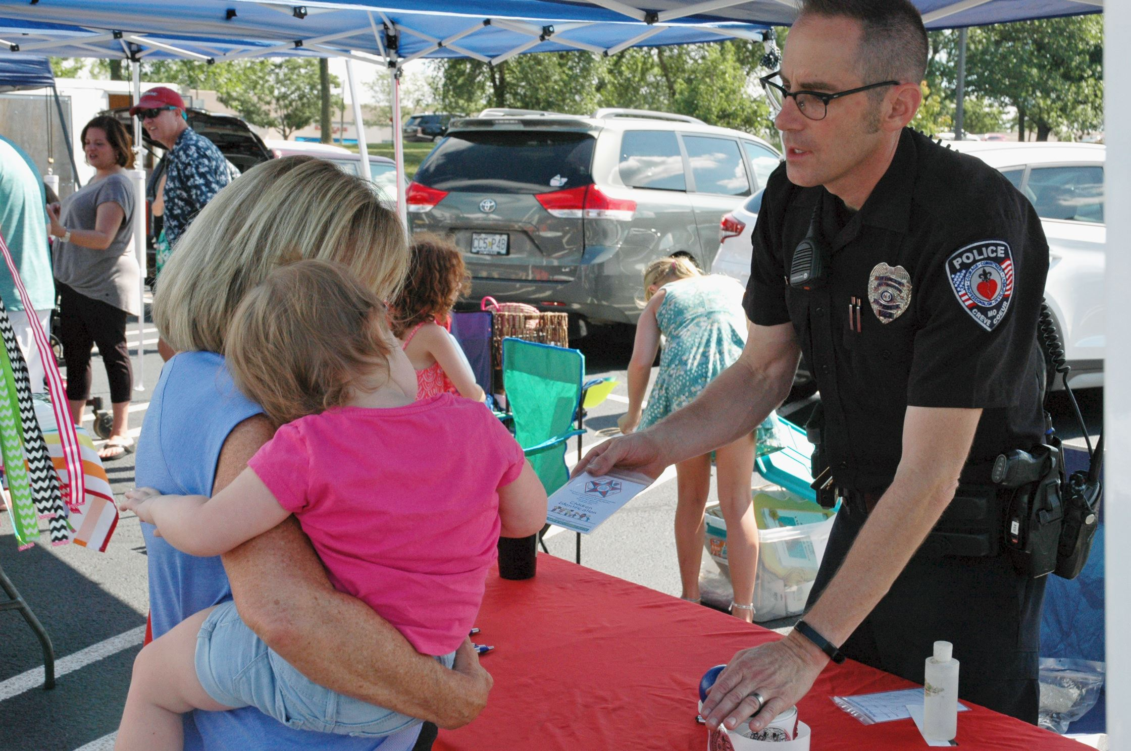 Creve Coeur police officer handing out child identification kits