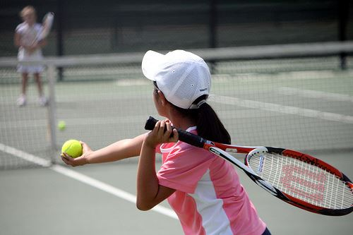 Girl serving tennis ball
