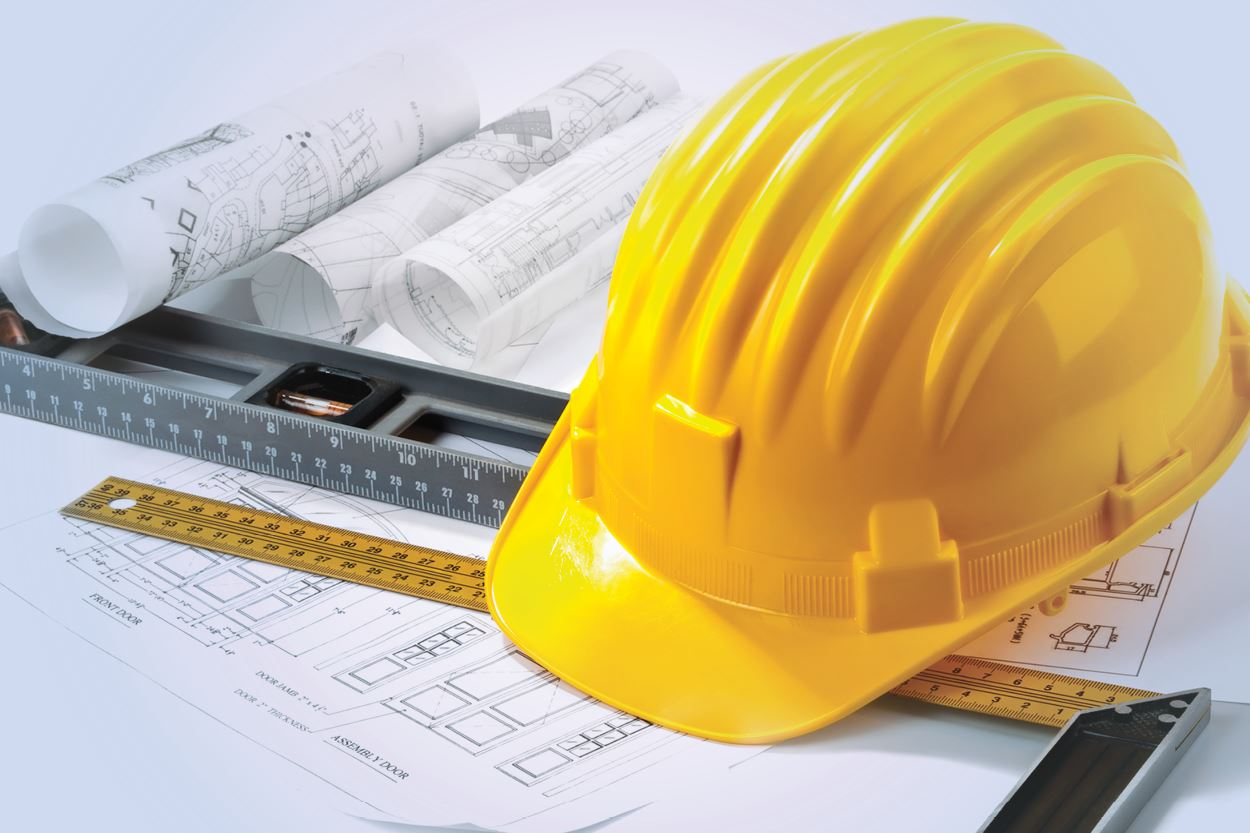 Construction hat on top of blueprints and ruler
